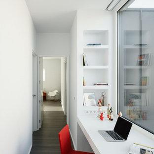 Ejemplo de despacho moderno con paredes blancas, suelo de madera oscura, escritorio empotrado y suelo gris