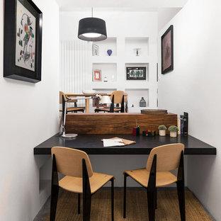 Imagen de despacho actual, de tamaño medio, con paredes blancas, suelo de cemento, escritorio empotrado y suelo gris