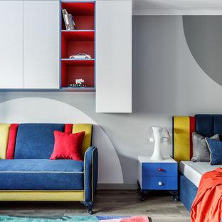 Пример оригинального дизайна: большая нейтральная детская в современном стиле с рабочим местом, паркетным полом среднего тона, обоями на стенах, серыми стенами и серым полом для подростка