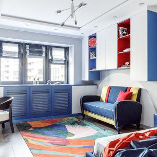 Bild på ett stort funkis könsneutralt tonårsrum kombinerat med skrivbord, med mellanmörkt trägolv, grå väggar och grått golv