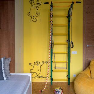 Exemple d'une salle de jeux d'enfant tendance avec un mur jaune, un sol en liège et un sol marron.