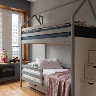 Immagine di una cameretta per bambini minimal con pareti grigie, pavimento in legno massello medio e pavimento marrone