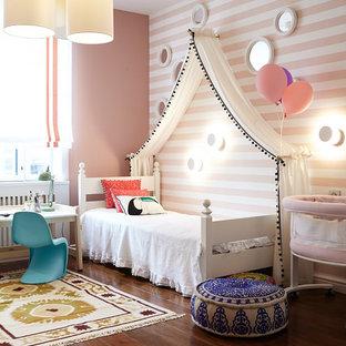 Ejemplo de dormitorio infantil de 4 a 10 años, tradicional, de tamaño medio, con paredes rosas, suelo marrón y suelo de madera oscura