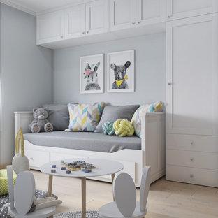 Immagine di una piccola cameretta per bambini da 1 a 3 anni scandinava con pavimento in laminato, pavimento beige e pareti bianche