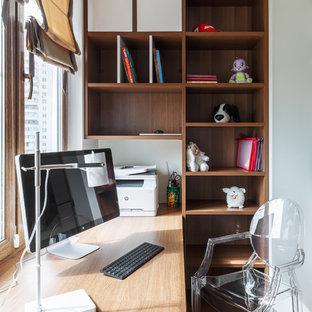 Aménagement d'une chambre de fille de 4 à 10 ans contemporaine de taille moyenne avec un bureau, un mur blanc, un sol en vinyl et un sol beige.