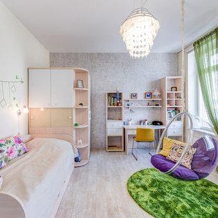 Cette image montre une chambre de fille de 4 à 10 ans design de taille moyenne avec un bureau, un mur beige et un sol en liège.