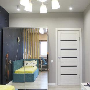 Esempio di una cameretta da bambino da 4 a 10 anni scandinava di medie dimensioni con pareti grigie, pavimento in laminato e pavimento beige