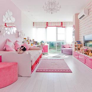 На фото: детская среднего размера в современном стиле с спальным местом, розовыми стенами, полом из ламината и белым полом для ребенка от 4 до 10 лет, девочки с