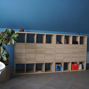 Großes Industrial Kinderzimmer mit Spielecke, blauer Wandfarbe, Porzellan-Bodenfliesen und grauem Boden in Sonstige