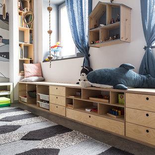 На фото: нейтральная детская с игровой в скандинавском стиле с разноцветными стенами и серым полом для ребенка от 1 до 3 лет