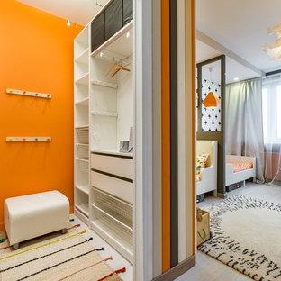 Aménagement d'une chambre neutre de 4 à 10 ans scandinave avec un mur orange, un sol en bois clair et un sol gris.