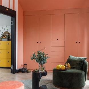Foto di una cameretta per bambini da 4 a 10 anni design di medie dimensioni con pavimento in laminato e pareti rosa