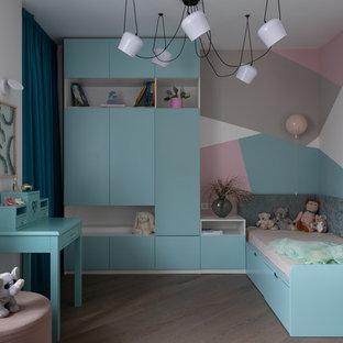 На фото: детская в современном стиле с разноцветными стенами, паркетным полом среднего тона и бежевым полом для девочки с