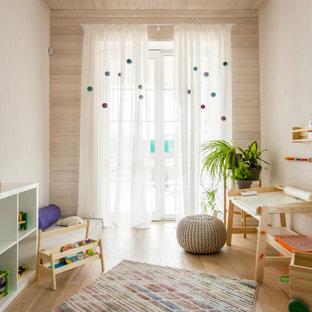 Modern inredning av ett barnrum, med beige väggar, ljust trägolv och beiget golv