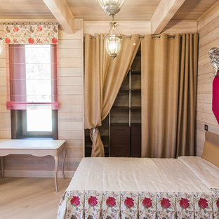 This is an example of a small country kids' bedroom for kids 4-10 years old and girls in Moscow with beige walls and light hardwood floors.