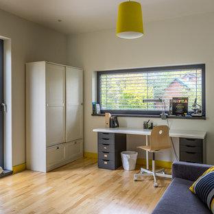 На фото: детская среднего размера в скандинавском стиле с рабочим местом, белыми стенами, светлым паркетным полом и бежевым полом для мальчика, подростка с