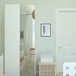 Immagine di una piccola cameretta per bambini scandinava con pareti verdi e pavimento in laminato
