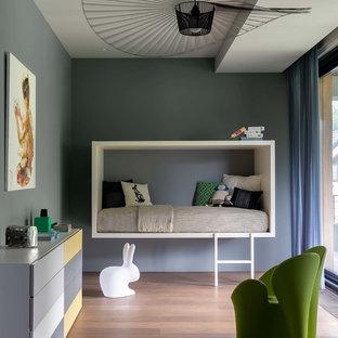 Inspiration för moderna könsneutrala barnrum kombinerat med sovrum, med grå väggar, mellanmörkt trägolv och brunt golv