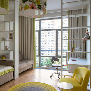 Esempio di una cameretta da bambina minimal con pareti beige e pavimento in legno massello medio