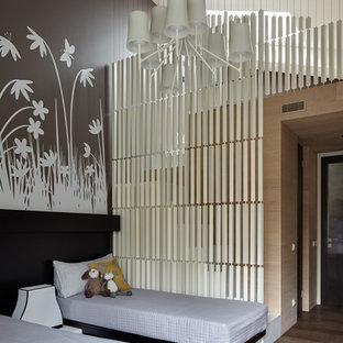 Immagine di una cameretta per bambini minimal con pavimento in legno massello medio, pareti marroni e pavimento marrone