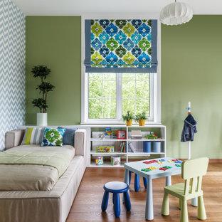 Ispirazione per una cameretta per bambini minimal con pareti verdi, pavimento in legno massello medio e pavimento marrone
