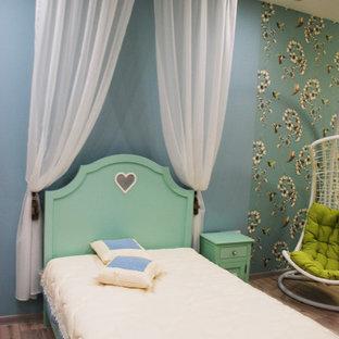 Immagine di una cameretta per bambini da 4 a 10 anni industriale con pareti verdi, pavimento in laminato e pavimento grigio