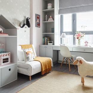 Aménagement d'une chambre de fille de 4 à 10 ans contemporaine de taille moyenne avec un bureau, un mur gris, un sol en bois brun et un sol gris.