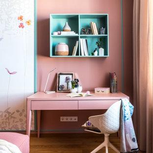 Inspiration för moderna flickrum kombinerat med skrivbord, med rosa väggar, mellanmörkt trägolv och brunt golv