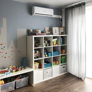 Foto di una cameretta per bambini da 4 a 10 anni nordica di medie dimensioni con pareti blu, pavimento in laminato e pavimento marrone