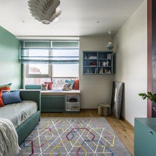 Ejemplo de dormitorio infantil actual con paredes verdes, suelo de madera en tonos medios y suelo marrón