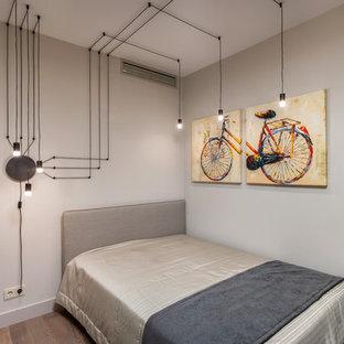 Foto de dormitorio infantil contemporáneo, de tamaño medio, con paredes grises, suelo laminado y suelo marrón