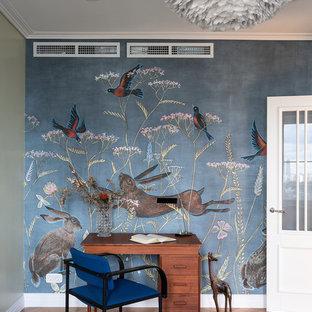 Inspiration pour une chambre neutre vintage avec un bureau, un mur bleu, un sol en bois brun, un sol marron et du papier peint.