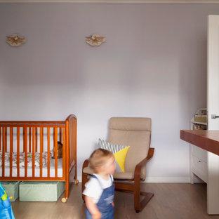 Foto di una cameretta per bambini da 1 a 3 anni di medie dimensioni con pareti viola, pavimento in laminato e pavimento beige