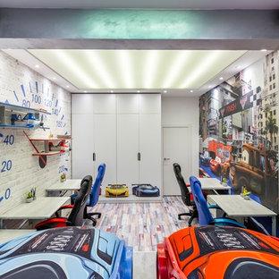 Foto di una cameretta per bambini da 4 a 10 anni industriale di medie dimensioni con pareti grigie, pavimento in sughero e pavimento multicolore
