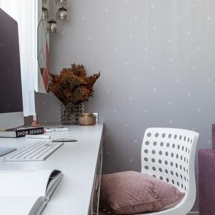 Foto på ett mellanstort funkis könsneutralt tonårsrum kombinerat med skrivbord, med grå väggar, laminatgolv och grått golv