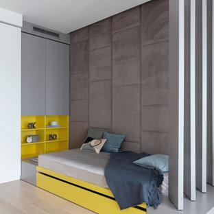 Esempio di una cameretta per bambini contemporanea con pareti beige, parquet chiaro e pavimento beige