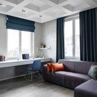 На фото: детская в современном стиле с рабочим местом, серыми стенами, паркетным полом среднего тона, серым полом и правильным освещением для подростка, мальчика с