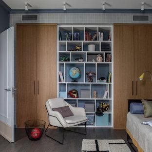 Immagine di una cameretta per bambini minimal con pareti grigie, pavimento in legno massello medio, pavimento marrone e carta da parati