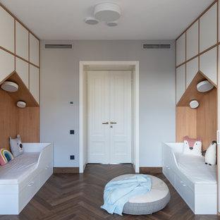 На фото: нейтральная детская среднего размера в современном стиле с спальным местом, серыми стенами, паркетным полом среднего тона и коричневым полом