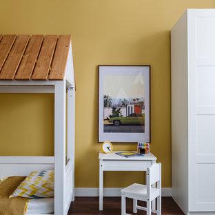 Exemple d'une chambre d'enfant de 1 à 3 ans tendance de taille moyenne avec un sol en bois foncé et un mur jaune.