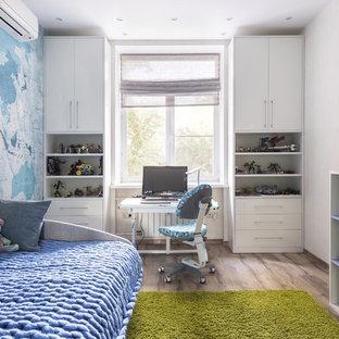 Idéer för mellanstora funkis pojkrum, med brunt golv, blå väggar och laminatgolv
