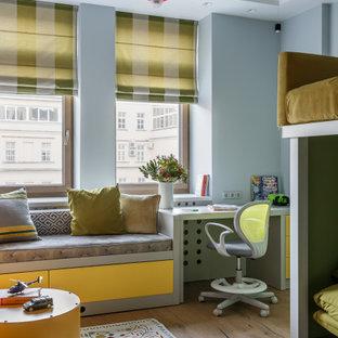 Immagine di una cameretta per bambini da 4 a 10 anni minimal di medie dimensioni con pareti blu, parquet chiaro e pavimento beige