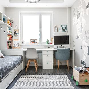 На фото: нейтральная детская в скандинавском стиле с рабочим местом, серыми стенами, серым полом и темным паркетным полом с
