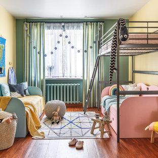 Неиссякаемый источник вдохновения для домашнего уюта: нейтральная детская среднего размера в современном стиле с желтыми стенами, полом из ламината и коричневым полом для ребенка от 4 до 10 лет