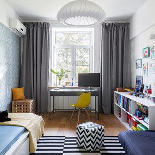 На фото: нейтральная детская в скандинавском стиле с рабочим местом, разноцветными стенами и светлым паркетным полом для ребенка от 4 до 10 лет с
