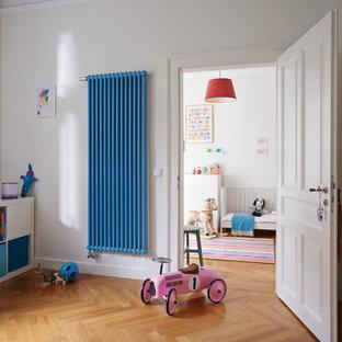 На фото: нейтральная детская в современном стиле с белыми стенами, паркетным полом среднего тона и коричневым полом
