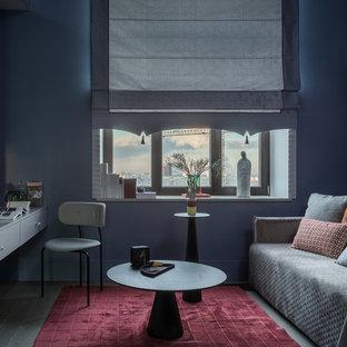 Inspiration för ett funkis könsneutralt barnrum kombinerat med skrivbord, med blå väggar, mörkt trägolv och svart golv