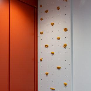 Immagine di una piccola cameretta per bambini da 1 a 3 anni contemporanea con pareti viola e pavimento in laminato