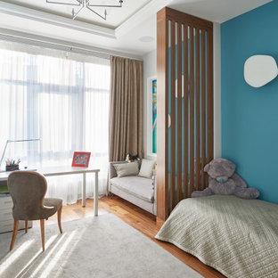 Inredning av ett modernt barnrum, med blå väggar, mellanmörkt trägolv och brunt golv