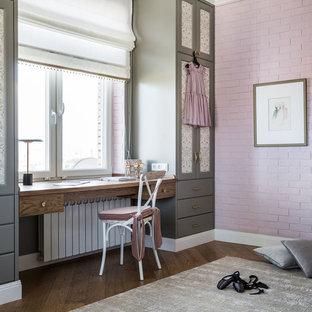 На фото: детская в стиле современная классика с рабочим местом, розовыми стенами, ковровым покрытием и коричневым полом для девочки